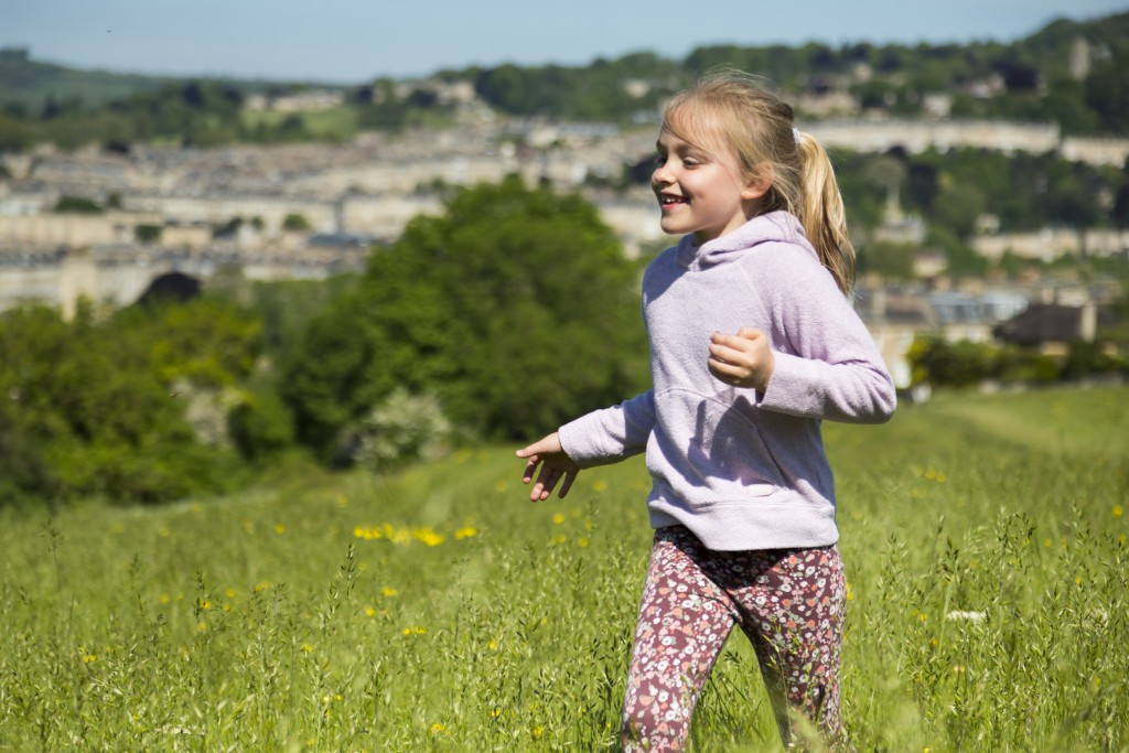 Girl running in the park at Bath Skyline, Prior Park Landscape Garden, Somerset