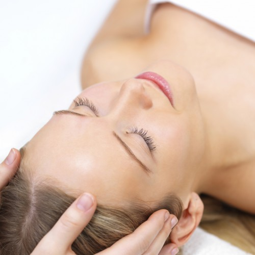 Hands massaging female face at the spa - Beautiful woman relaxing with a head massage at the beauty spa.